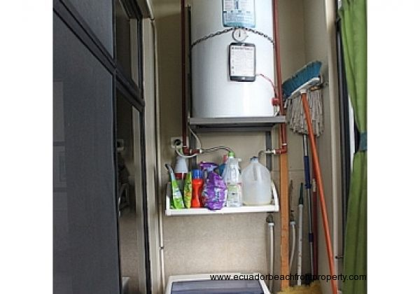 Utility room has a washing machine and electric water heater