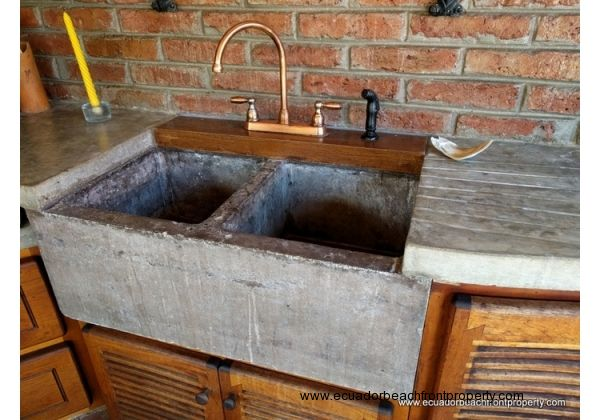 Copper fixture with a concrete countertop and deep double sink.