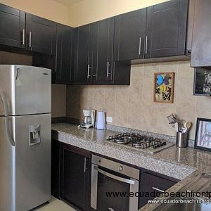Kitchen has granite countertops plus lower and upper cabinetry