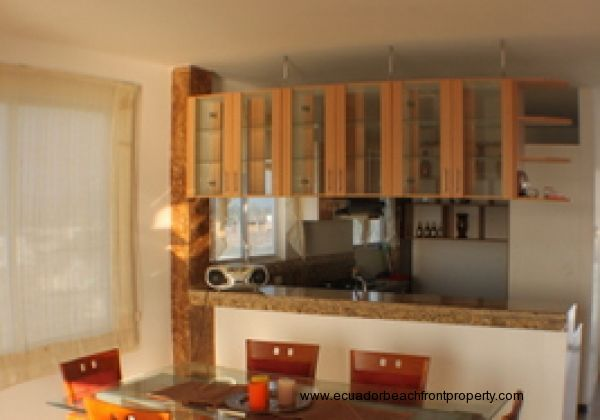 View from dining area to kitchen bar and into the kitchen