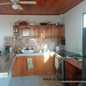 Kitchen with wood cabinetry and tile countertops