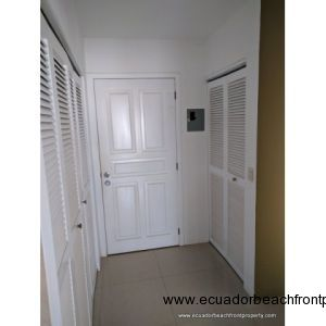 Condo entry with large pantry with shelving on left and laundry area on right