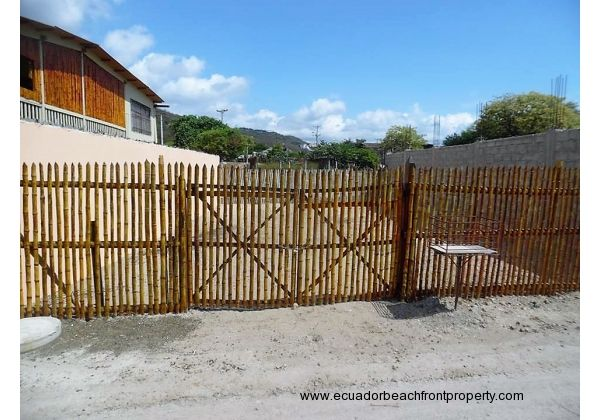 West lot. 2 sided bamboo fencing, front with gate. 2 sides are 10 1/2 foot cement block wall
