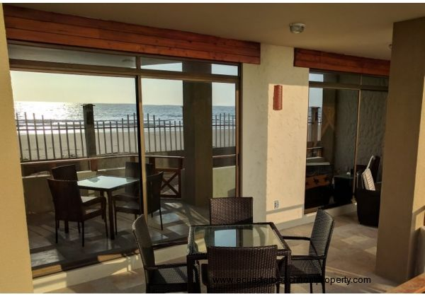 Spacious beachfront patio with dining table and chairs plus two comfy chairs with ottomans