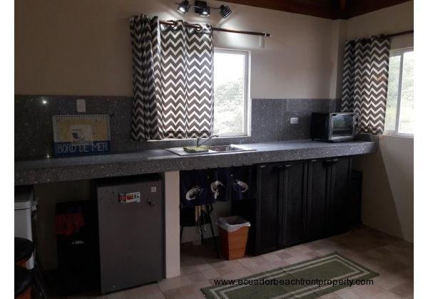 Upstairs kitchen is equipped with a small refrigerator, sink, and gas stovetop