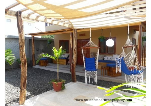 Front yard has a carport/pergola outfitted with Sun Sail shades and hammock chairs