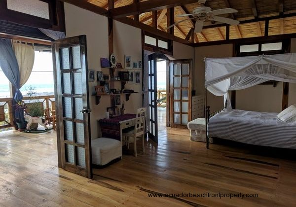 Large master bedroom with sitting area, walk-in closet, ensuite bath, and 2 double doors leading to the beachfront balcony