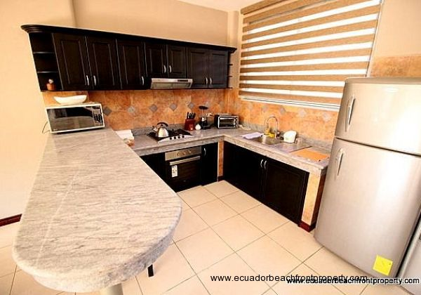 Kitchen has granite countertops, wood cabinetry, 4-burner gas stovetop, stainless sink and refrigerator