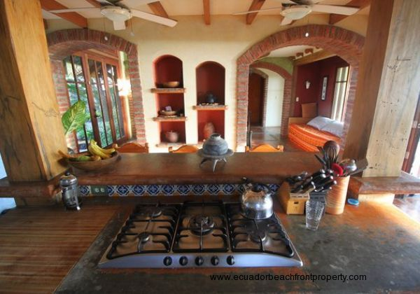 Kitchen opens to a living area with recessed shelving, broad archways, and large picture windows to maximizing views towards tropical gardens and the beach