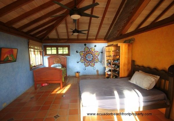 Spacious upstairs bedroom with vaulted wood ceiling and painted mandala