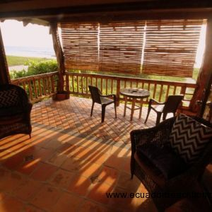 Sitting area of the master bedroom with bamboo sun shade lowered against the setting sun