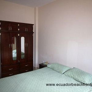 Bedroom with queen bed, armoire, and AC