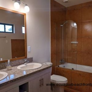 Full bath with double sinks and a bath tub.