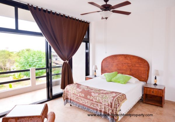 Spacious master bedroom with balcony overlooking fruit trees and tropical landscaping