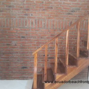 Staircase with a decorative feature brick wall up to the first floor.