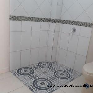 Spacious bathroom, fully tiled.