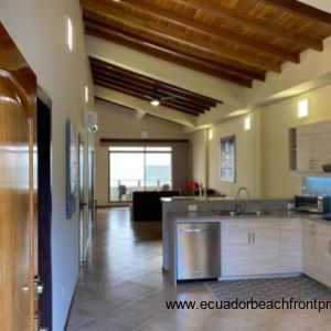 View from the front entrance of the kitchen, dining and living space with the amazing wraparound view of the pool to the side and ocean at the far end from the living space.