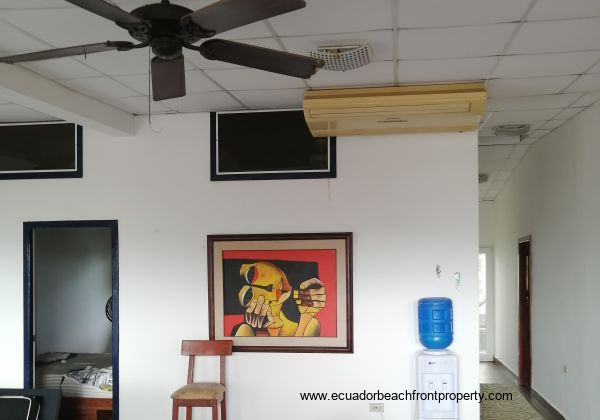 Open plan living area with AC unit and ceiling fans.
