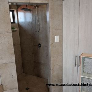 Fully tiled bathroom and shower cubicle.